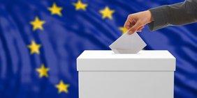 Mann steckt Umschlag in eine Wahlurne, die vor einer Europa-Flagge steht