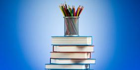 Buntstifte und Bücherstapel auf blauem Hintergrund