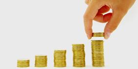 Hand einer Frau nimmt Münzen von Geldstapel