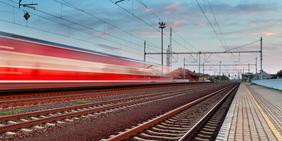 Schnell durchfahrender Zug an Bahnhof